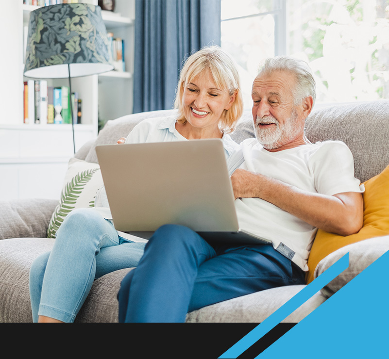 smiling woman and man looking at laptop
